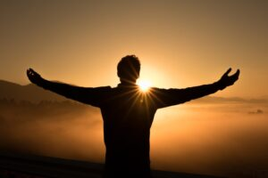 man with outstretched arms in awakening to the sun