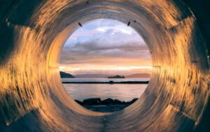 viewing the ocean through a steel tunnel full of light