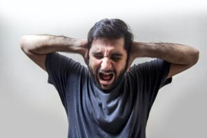 man covering his ears and screaming with anger