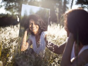 woman holding mirror and smiling at herself